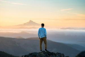 Mann auf Berg mit Aussicht